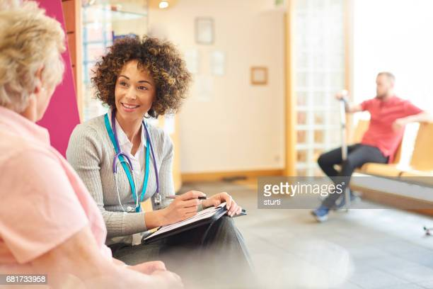 chatting to senior patient in the waiting room - female doctor stock photos and pictures