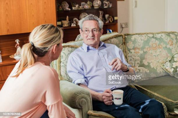 chatting with his carer at home - social services stock pictures, royalty-free photos & images