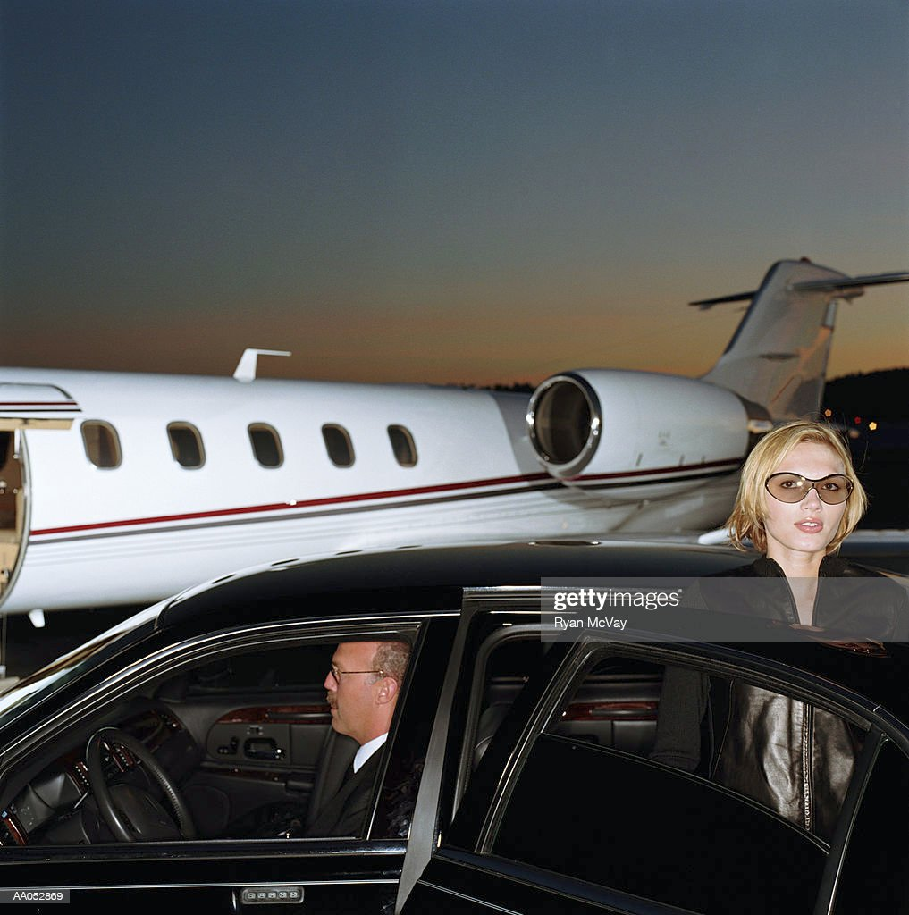 Chauffeur dropping young woman off on airfield, lear jet in background : Stock Photo