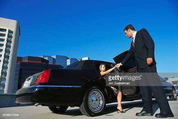 Chauffeur Helping Woman out of Limousine