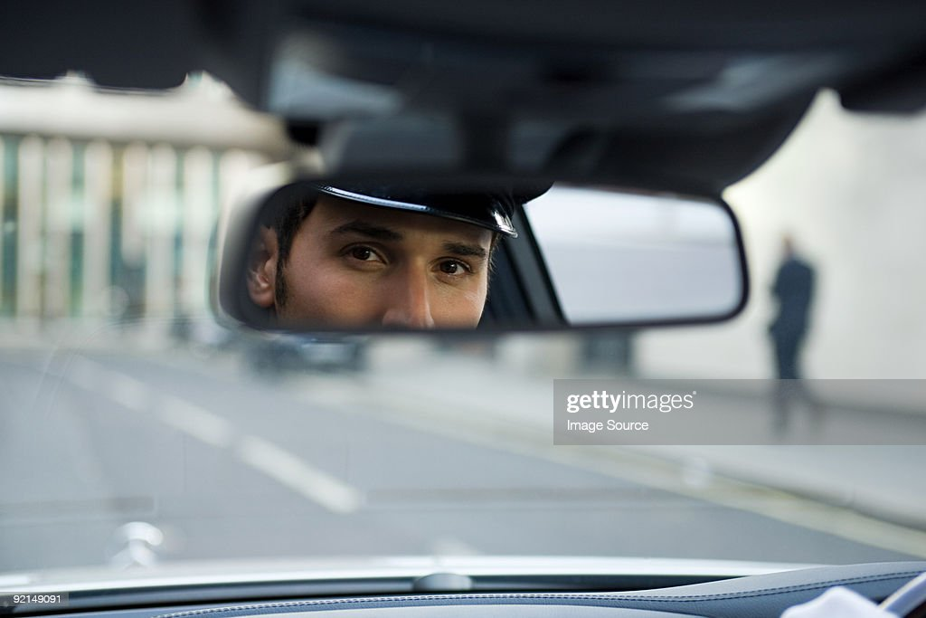 Chauffeur looking in rear view mirror : Stock Photo