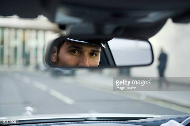 Chauffeur looking in rear view mirror