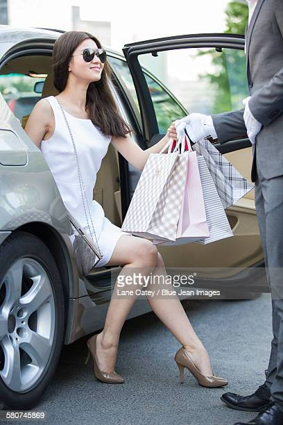 Chauffeur opening car door for a young woman