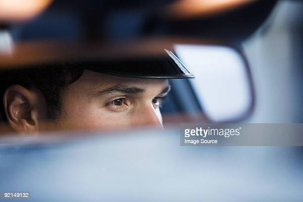 Chauffeur reflected in rear view mirror