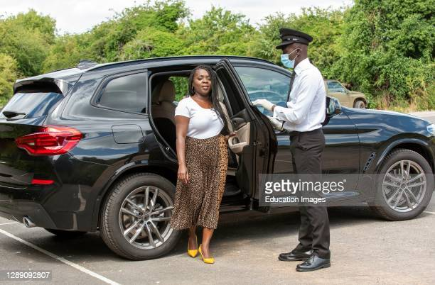 Chauffeur wearing a facemask opens the car door for his client during Covid-19, England, UK.