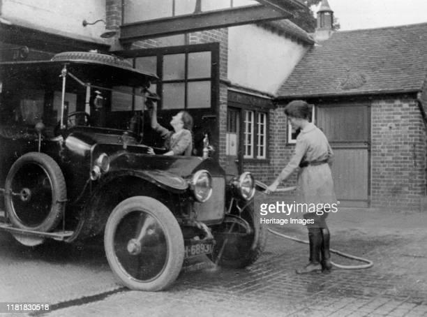 Chauffeuse washing car with hosepipe circa 1911. Creator: Unknown.