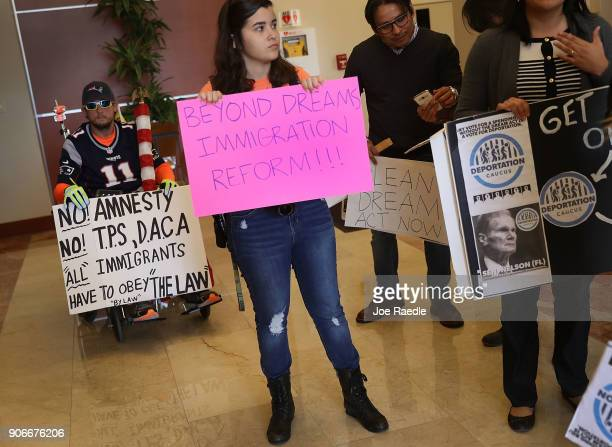 Chaunce O'Connor holds a sign that reads 'No Amnesty No TPS DACA 'All immigrants have to obey the law' as Mariantonieta Chavez and others attempt to...