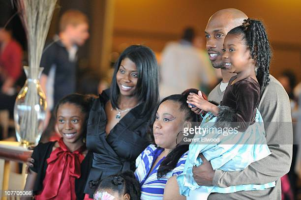 Chauncey Billups of the Denver Nuggets and his wife Piper Billups pose for a photo with a family from the Warren Village during a Holiday Party on...