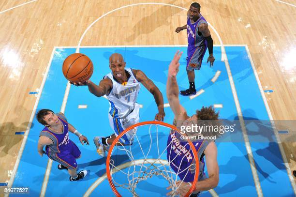 Chauncey Billups of the Denver Nuggets shoots a layup against Steve Nash and Robin Lopez of the Phoenix Suns during the game at Pepsi Center on...