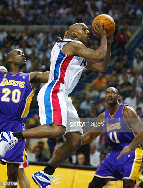 Chauncey Billups of the Detroit Pistons leaps past Gary Payton and Karl Malone of the Los Angeles Lakers during the first quarter in game four of the...