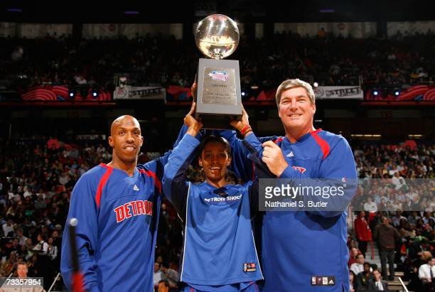 Chauncey Billups of the Detroit Pistons Swin Cash of the Detroit Shock and NBA legend Bill Laimbeer celebrate with the trophy after winning the Haier...