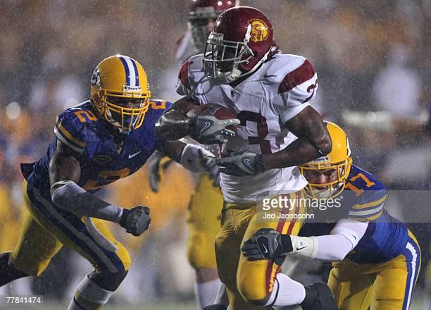 Chauncey Washington of the USC Trojans runs against Bernard Hicks and Chris Conte of the California Golden Bears during an NCAA football game at...