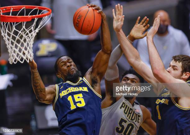 Chaundee Brown of the Michigan Wolverines grabs the rebound against Trevion Williams of the Purdue Boilermakers during the second half at Mackey...