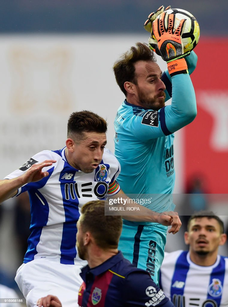 Chaves' Portuguese goalkeeper Antonio Filipe (R) catches a ball beside Porto's Mexican midfielder Hector Herrera during the Portuguese league football match between GD Chaves and FC Porto at the Municipal Eng. Manuel Branco Teixeira stadium in Chaves on February 11, 2018. /