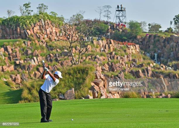 Chawrasia of India plays his approach shot on the 17th hole during the continuation of the delayed third round the Hero Indian Open at Dlf Golf and...