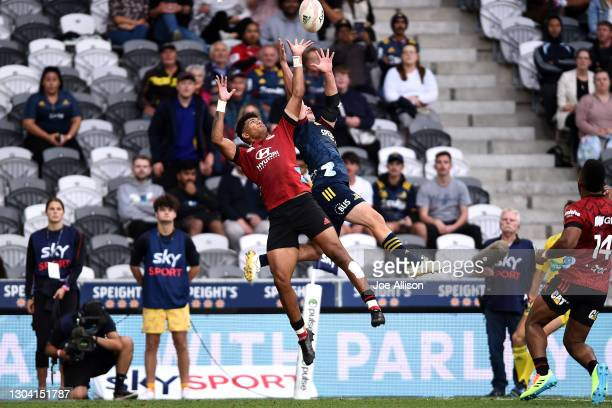 Chay Fihaki of the Crusaders and Connor Garden-Bachop of the Highlanders contest for the ball during the round one Super Rugby Aotearoa match between...