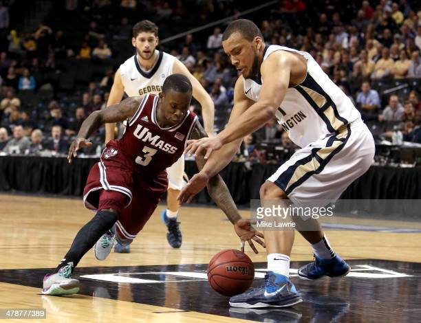 Chaz Williams of the Massachusetts Minutemen and Kevin Larsen of the George Washington Colonials go for a loose ball in the second half during the...