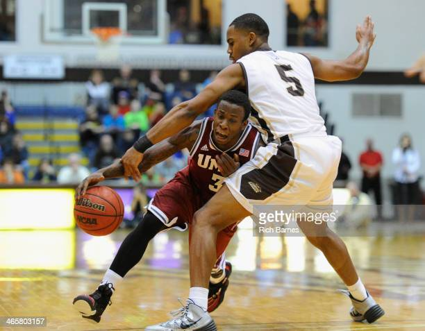 Chaz Williams of the Massachusetts Minutemen gets tangled up with Jordan Gathers of the St. Bonaventure Bonnies while driving to the basket during...