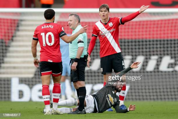 Che Adams and Jannik Vestergaard of Southampton disagree with referee Jonathan Moss after he awards a foul to Bruno Fernandes of Manchester United...