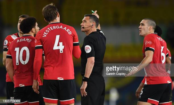 Che Adams, Jannik Vestergaard and Oriol Romeu of Southampton interact with Match Referee Andre Marriner during the Premier League match between Leeds...