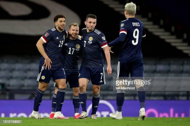Che Adams of Scotland celebrates with teammates John McGinn, Ryan Fraser and Lyndon Dykes after scoring their team's third goal during the FIFA World...