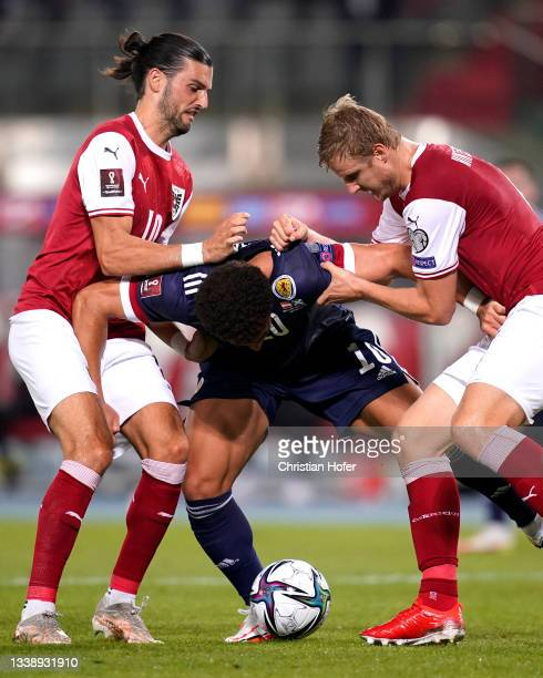 Che Adams of Scotland is fouled by Florian Grillitsch and Martin Hinteregger of Austria leading to a penalty being awarded during the 2022 FIFA World...