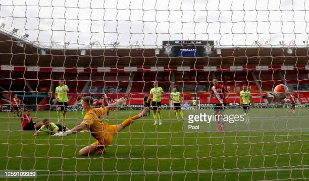 Che Adams of Southampton scores his team's second goal during past goalkeeper Dean Henderson of Sheffield United the Premier League match between...