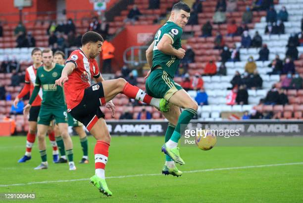 Che Adams of Southampton scores their team's first goal past John Egan of Sheffield United during the Premier League match between Southampton and...