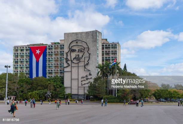 Che Guevara face outline and national flag on its front Tourists walking in big open space in front of a building with