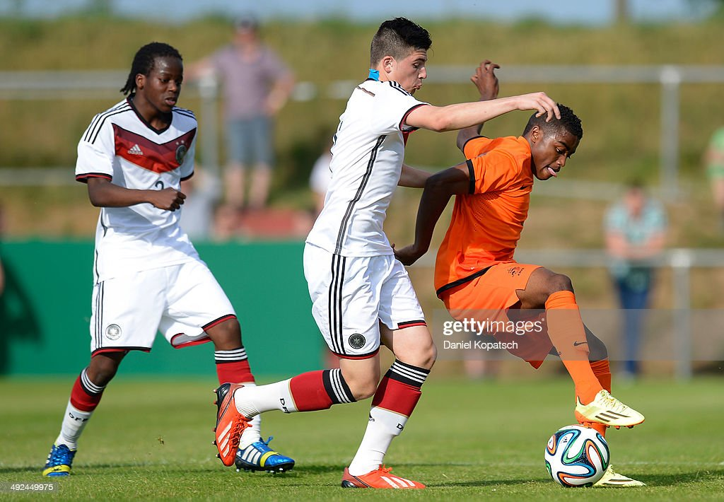 Che Nunnely of the Netherlands (R) is challenged by Nikos Zografakis of Germany during the international friendly U15 match between Germany and Netherlands on May 20, 2014 in Weingarten, Germany.