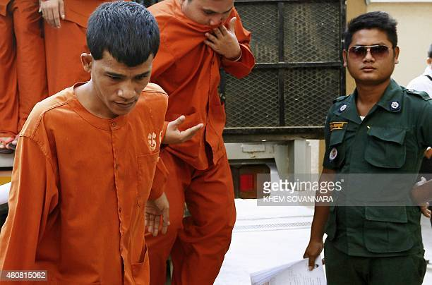 Chea Phin , a Cambodian man who confessed to the murder of a Dutch national and her child, walks with other prisoners as they are escorted by police...