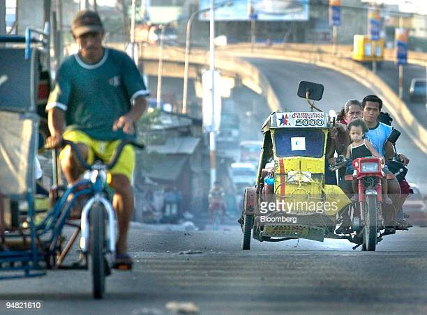 Cheap but effective motorized tricycles carry passengers and cargo on the busy polluted streets in central Manila Philippines March 22 2005