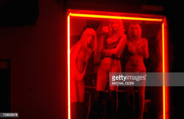 Prostitutes wait for clients behind a window of a brothel 14 December 2006 on a highway near the city of Cheb located on western CzechGerman border...
