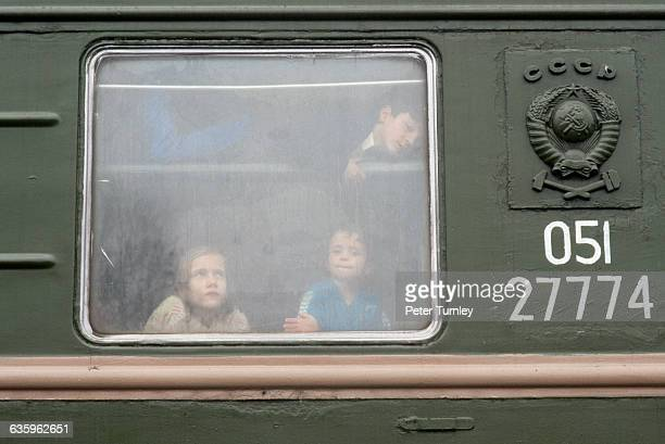 Chechen children look out a sleeping car window which is their temporary shelter after fleeing the war