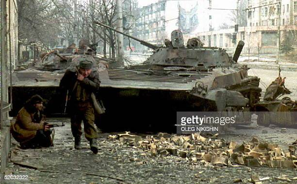 Chechen fighter runs for cover as another hides behind a destroyed Russian tank during fighting in Grozny 08 January Russian forces resumed shelling...