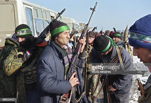 Chechen fighters prepare their weapons next to the buses where they keep a group of hostages 10 January 1996 in the region of Pervomaysk near the...