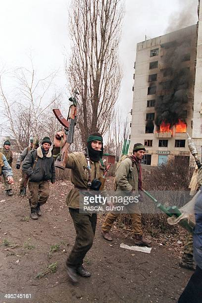 Chechen fighters walk past a building set on fire by a Russian rocket in downtown Grozny on January 13 1995 Russian artillery pounded Grozny all...