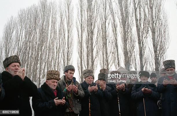 Chechen Muslim men pray and grieve at the funeral of a friend killed the day before in the conflict against Russia.