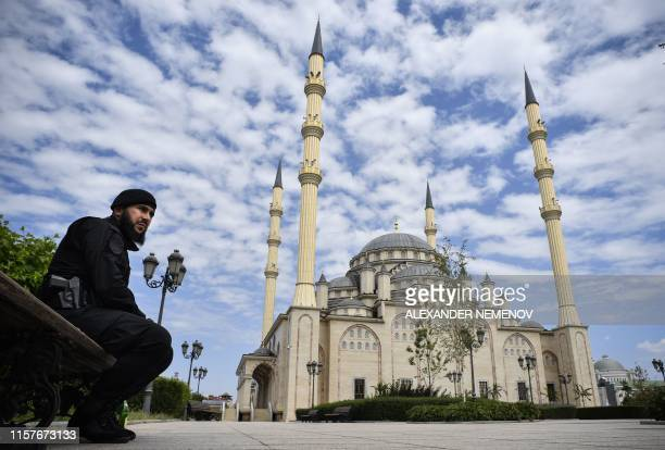A Chechen policeman guards in front of the Heart of Chechnya Akhmad Kadyrov Mosque in Grozny on July 26 2019