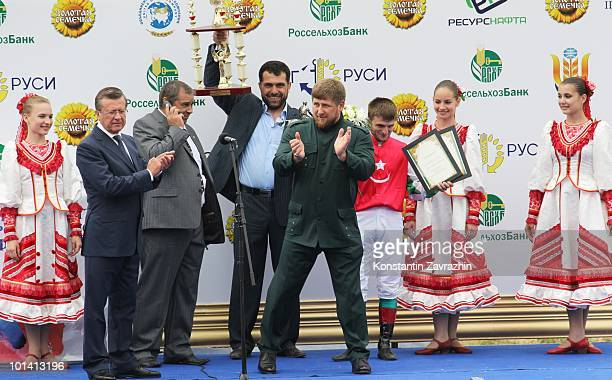 Chechen President Ramzan Kadyrov applauds as he collects the race prize after his horse Khorezm raced to victory in the prestigious 2400meter...