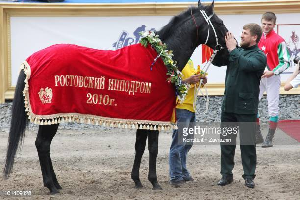 Chechen President Ramzan Kadyrov pets his horse Khorezm having watchede as it raced to victory in prestigious 2400meter President of the Russian...