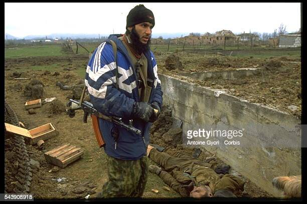 Chechen rebel in front of bodies of Russian soldiers killed during fights | Location Goiskoie Chechnya Russia