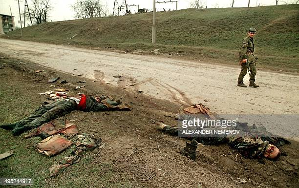A Chechen rebel passes 03 March 1996 by the bodies of Russian soldiers in Grozny capital of the breakaway southern republic of Chechnya Chechen...