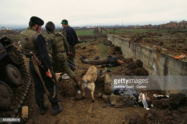 Chechen rebels in front of bodies of Russian soldiers killed during fights | Location Goiskoie Chechnya Russia