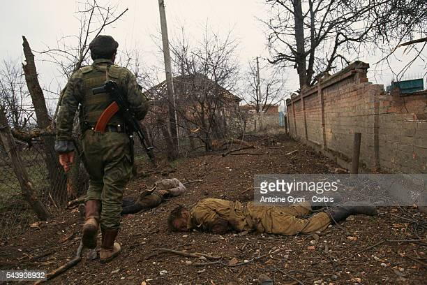 Chechen rebels walk past bodies of Russian soldiers killed during fights | Location Goiskoie Chechnya