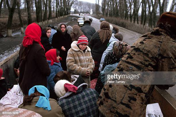 Chechen refugees flee the war in groups riding in the back of trucks