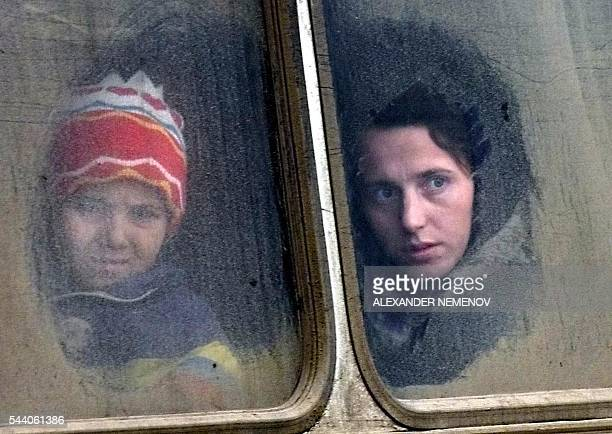 Chechen refugees look out from a bus window 27 December 1999 as they cross the ChechenIngush border check point after fleeing the warntorn Chechnyan...