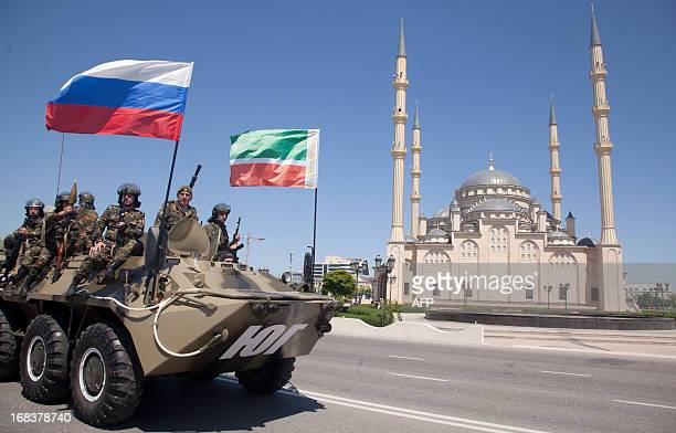Chechen special forces officers ride atop an armoured personnel carrier during Victory Day parade in front of the Akhmad Kadyrov Mosque in central...