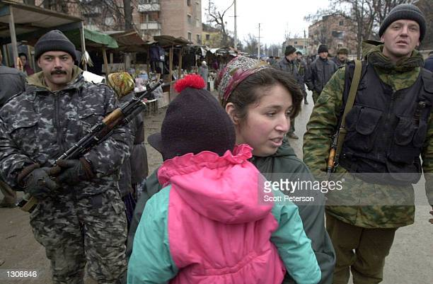 Chechen woman carries her child ahead of Russian troops on patrol in central Grozny November 23 capital of the breakaway republic of Chechnya....