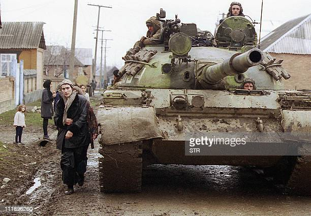 A Chechen woman passes by a tank of Russian federal troops on the main street of GehyChu village south from Grozny 16 February 2000 Russian forces...